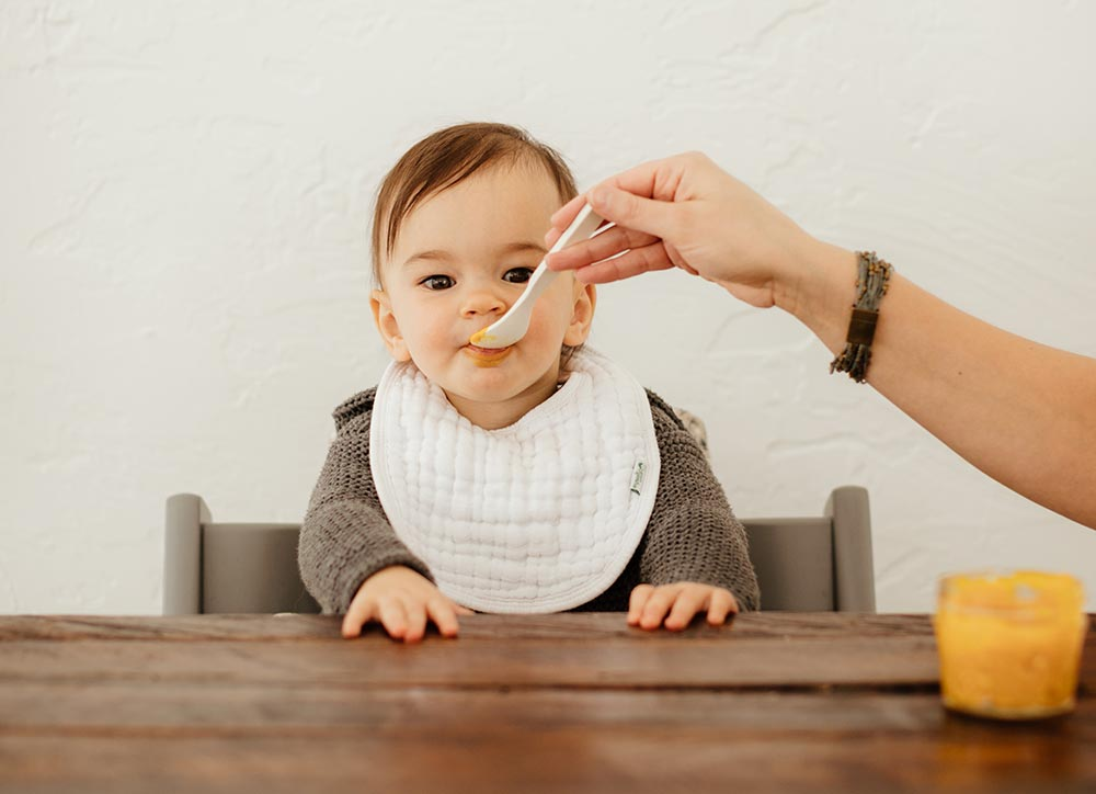 Spooning a puree into a baby's mouth.