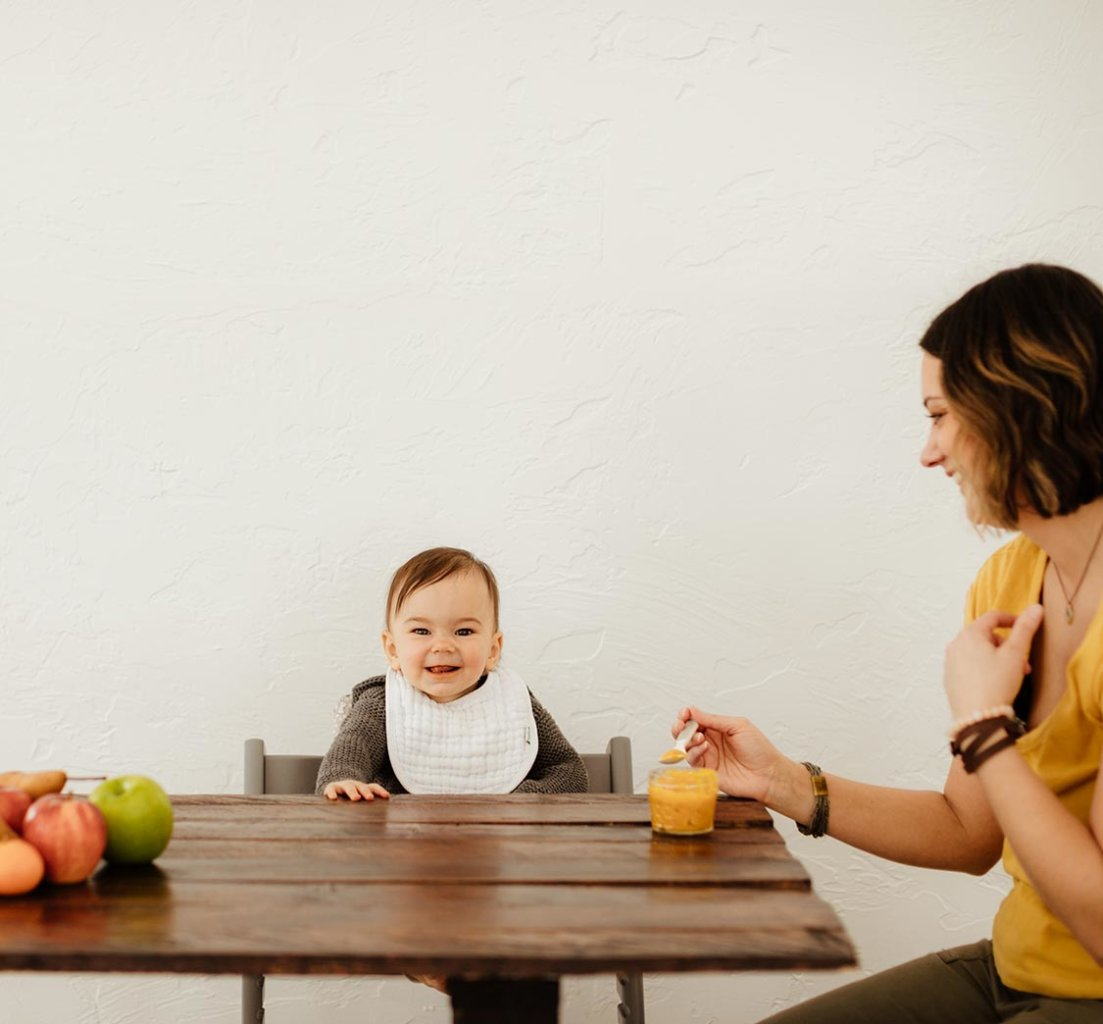 A baby and mom sitting at the table feeding baby puree from a small glass jar with a baby spoon.