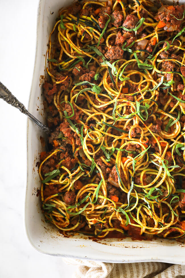Overhead image of zucchini noodle casserole in a large casserole dish with a serving spoon dug in.
