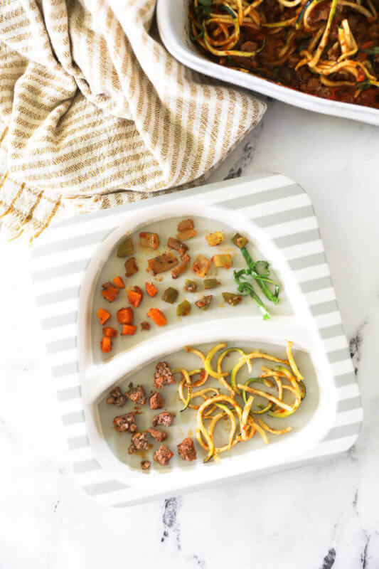 Image of a toddler plate made with zucchini casserole. Each ingredient is separated out in toddler sized pieces.