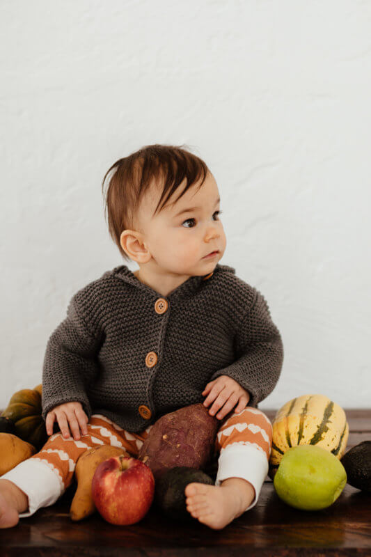 Baby sitting on a table looking off to the side surrounded by whole fruits and veggies.